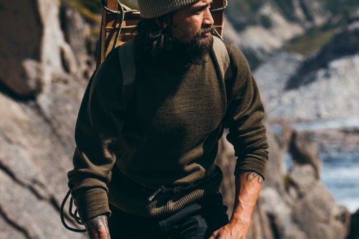 man in green sweater walking up a stony path