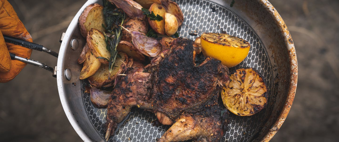 hand holding a camp pan with charred chukar meat and potatoes and charred lemons