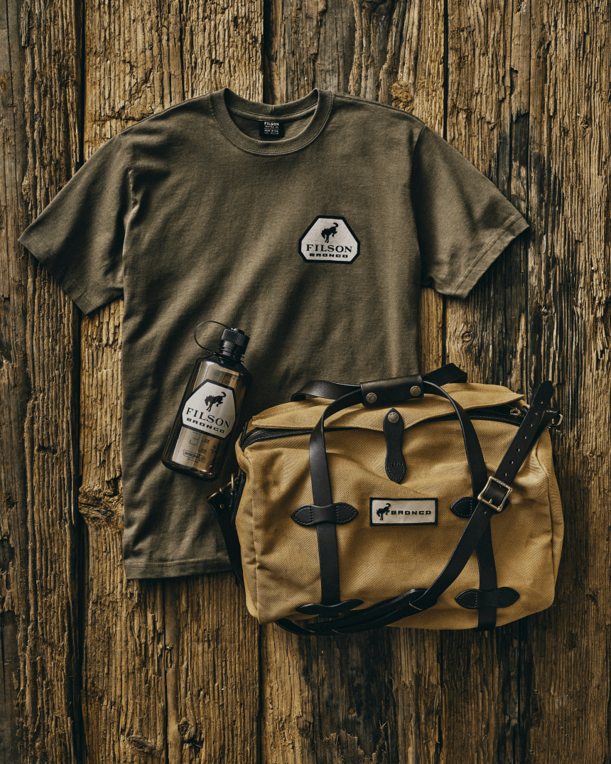 filson shirt, bottle, and duffel bag on a wood table