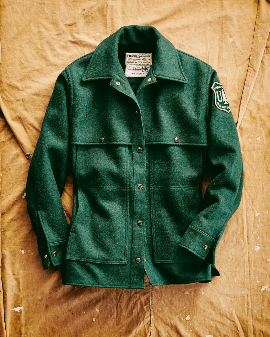 filson forestry service green jacket on a cloth surface