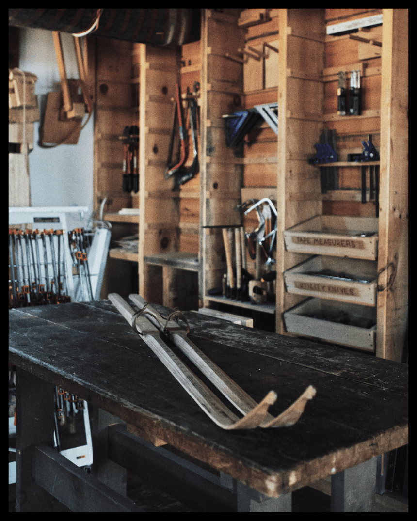 wooden skis laid out on a workbench in a ski making shop