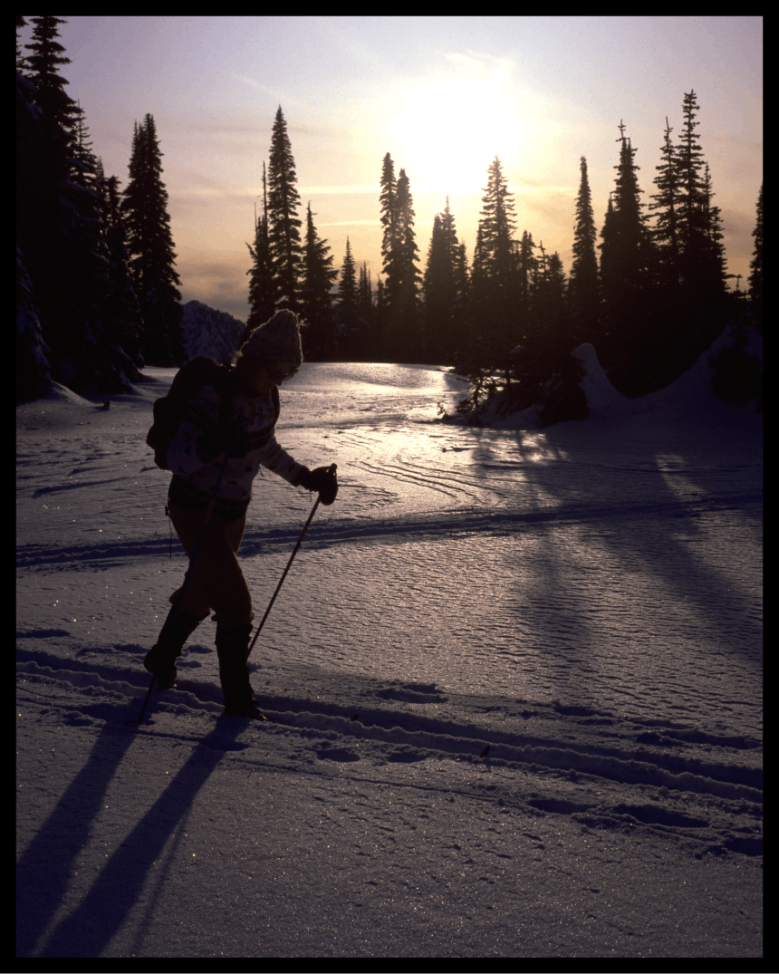 person trekking through snow at dusk on cross country skis in the snow