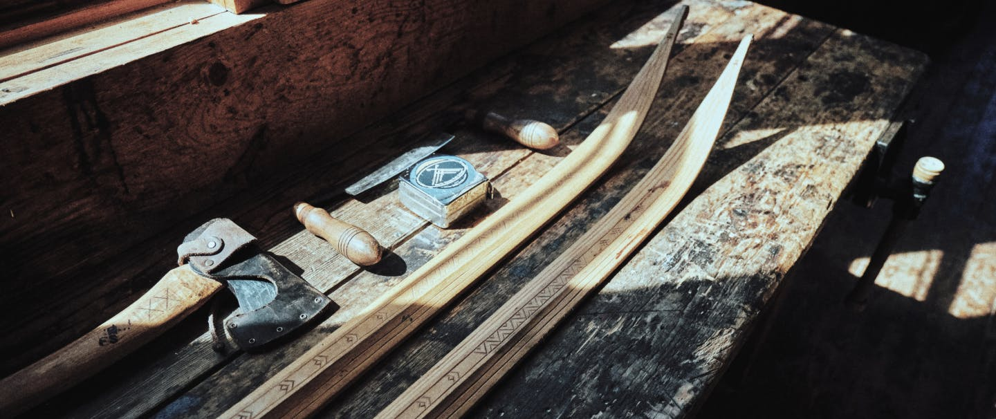 wooden cross country skis being built and honed on a wooden table