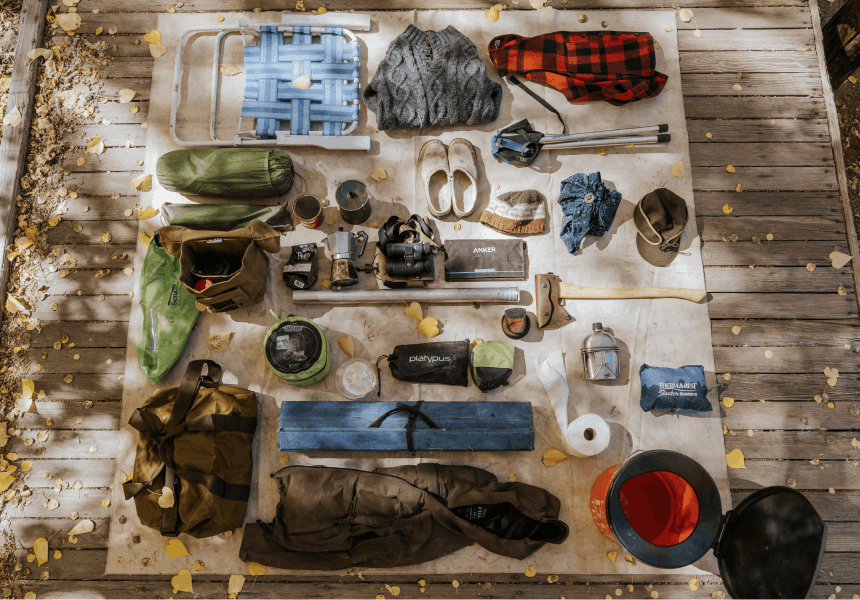 layout of various camping supplies laid out on a canvas sheet on a wooden deck