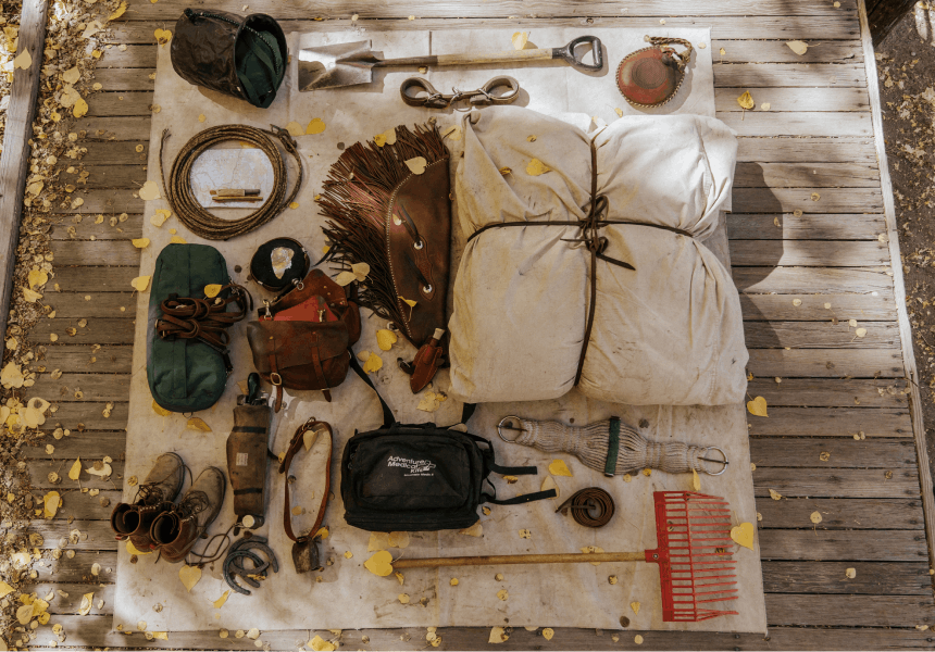 layout of pack mule supplies on a canvas sheet on a wooden deck