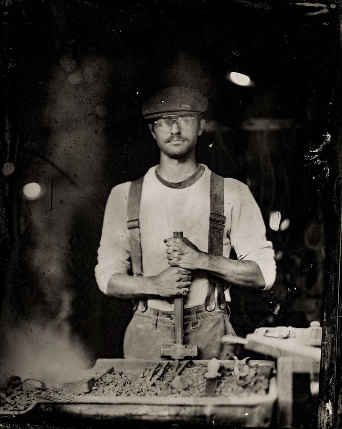 person standing at a forge holding a sledge hammer