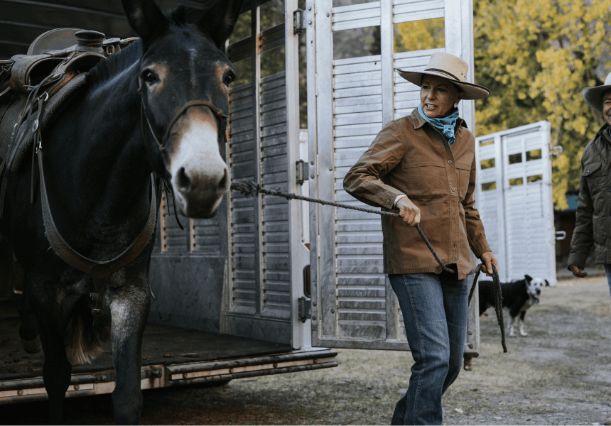 woman in tan hat and brown jacket leading a horse out of a livestock trailer