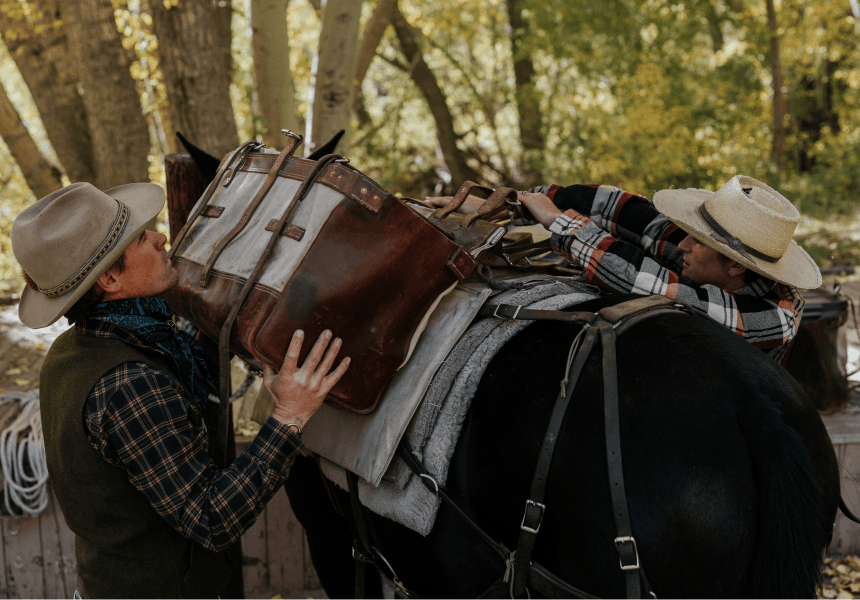 man and woman loading up a pack horse with saddle and saddle bags in the woods