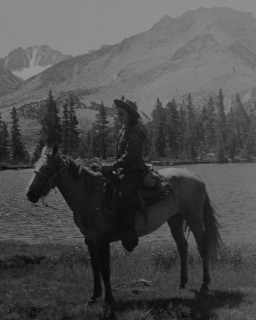 black and white image of woman on a horse with mountains in the background