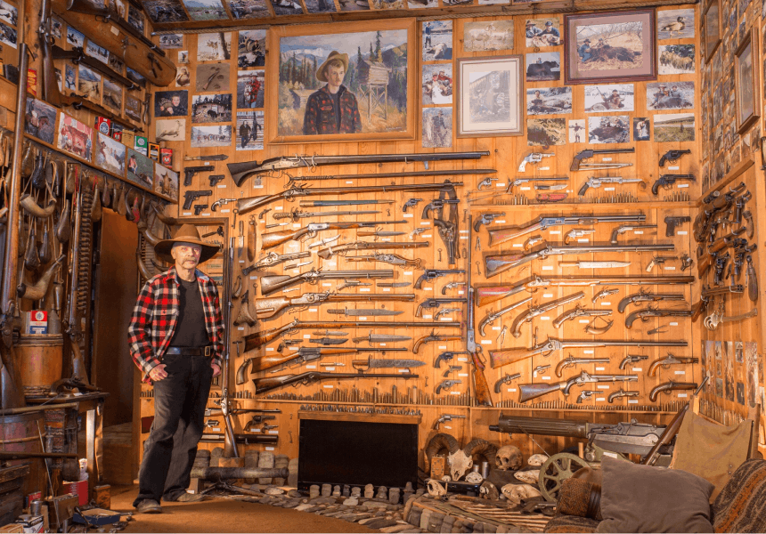 man standing in a room with a large number of mounted guns, knives, and paintings at the rainy pass lodge