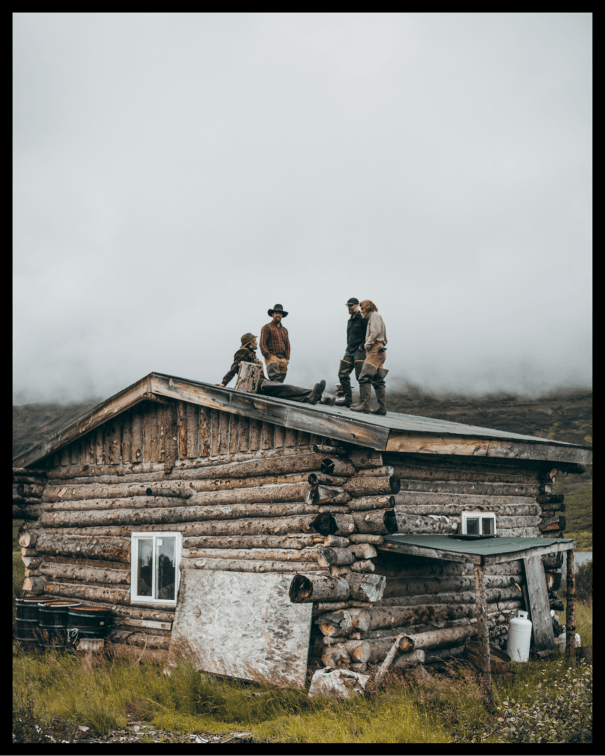 group of people standing on top of the roof of a log cabin