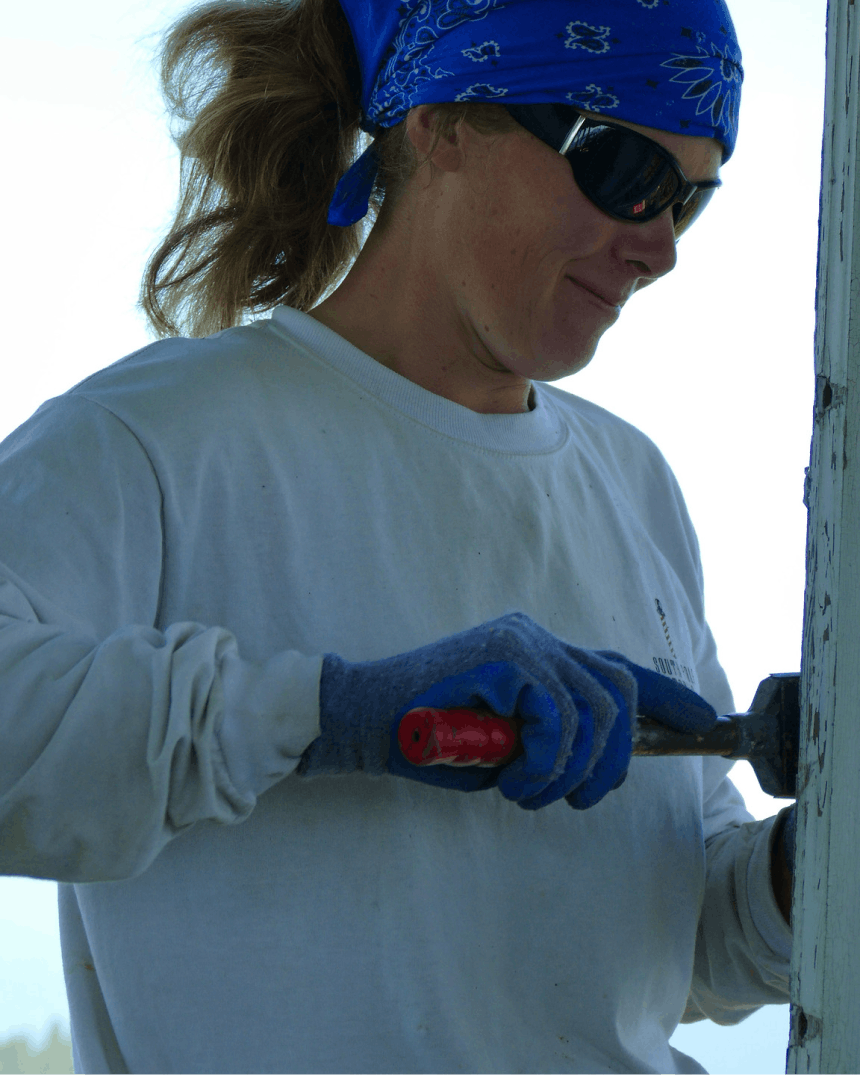 woman in blue bandanna, working on painting a wooden piece