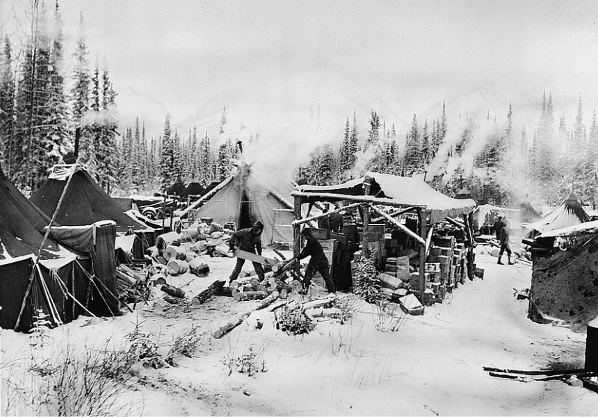 black and white image of people working in a campsite on the alcan highway, chopping wood outside of tents