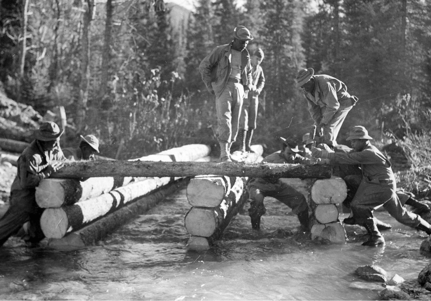 six workers building a structure out of large tree trunks on a river