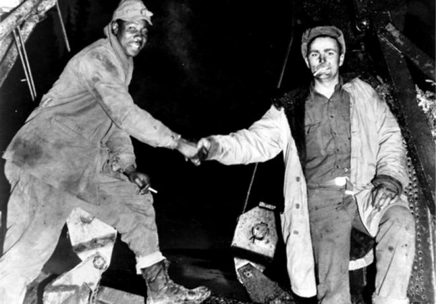 two men shaking hands wearing tarnished logger's uniforms