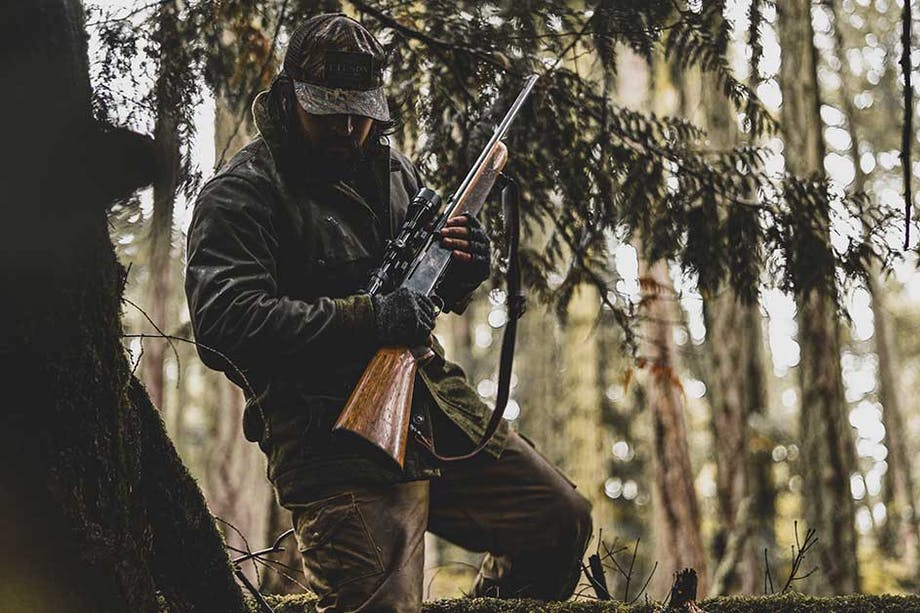 person in green coat and hat holding a rifle walking through a pine tree forest