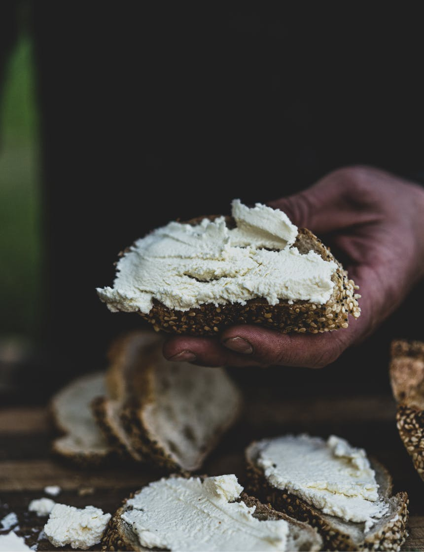 hand holding a piece of bread with farmer's cheese on it