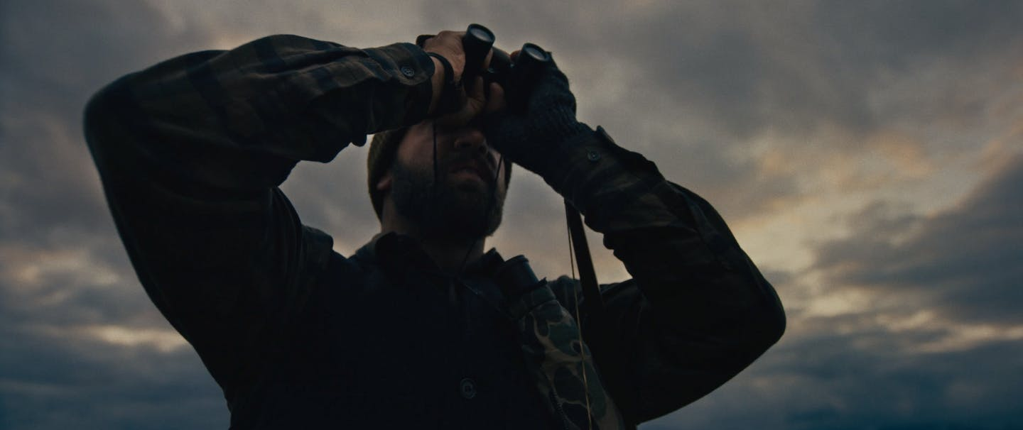 man holding field glasses looking through them under moody skies