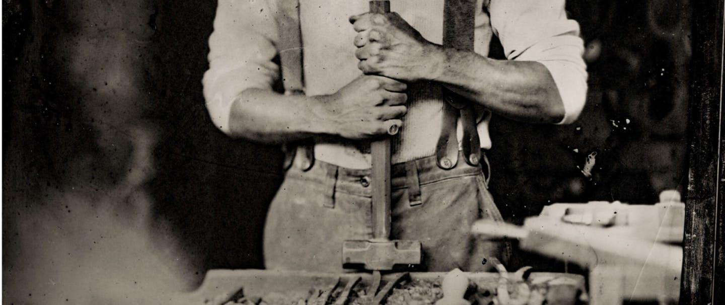 old black and white hands holding a sledge hammer