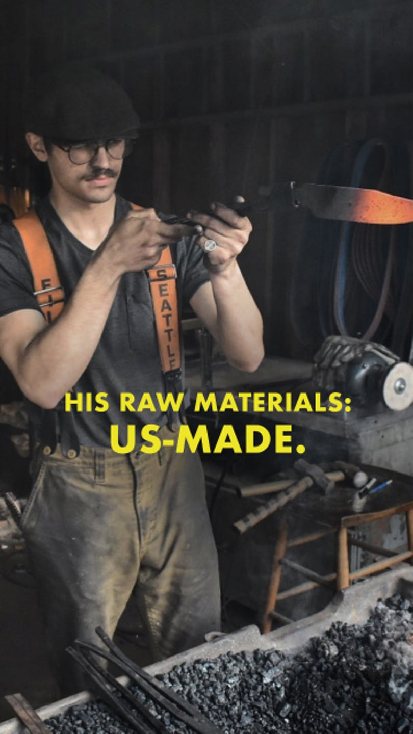 person working at a forge holding a red hot blade with tongs