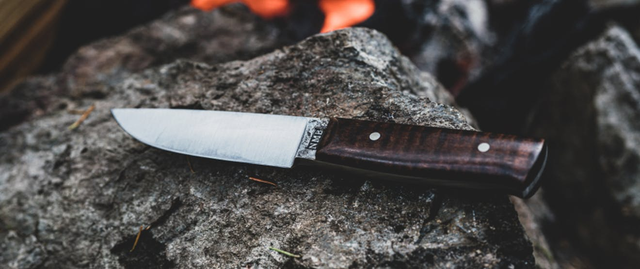 buck knife with wooden handle sitting on a rock in front of the coals of a fire