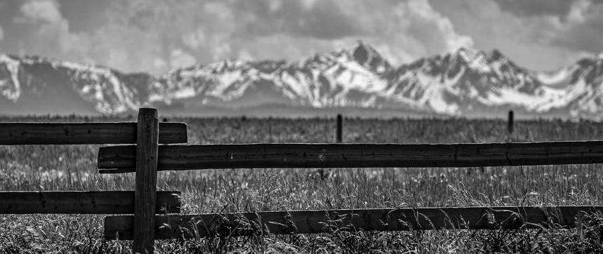 wooden fence in foreground of grassy field with snow capped mountains in distance
