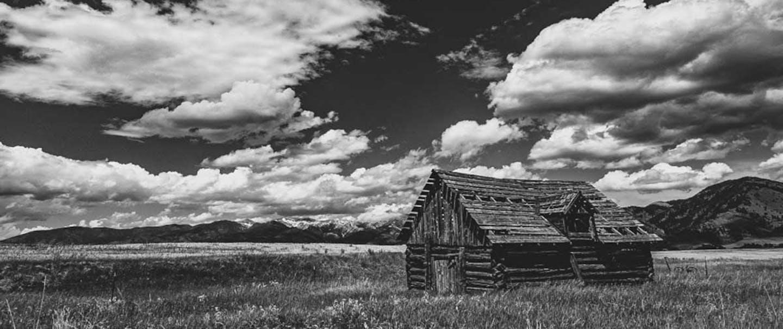 log cabin in a grassy field