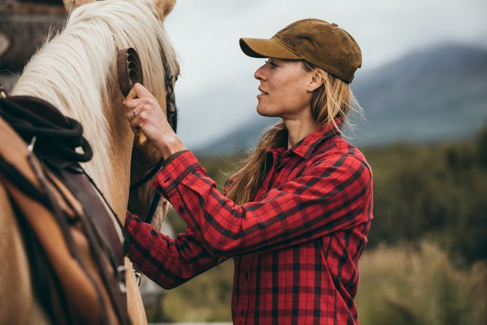 woman in black and red plaid shirt tends to a horse's mane