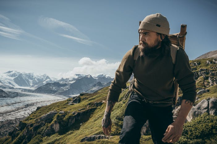 man in tan filson beanie and olive sweater hikes on green mountainside with snowy mountains in background
