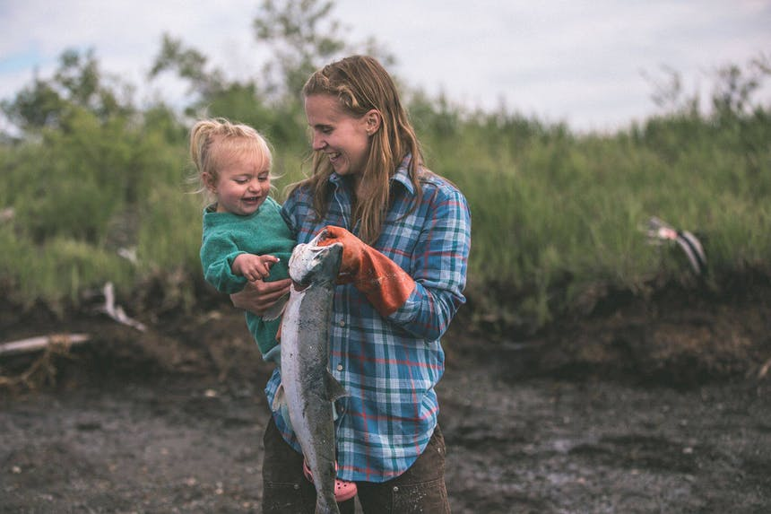 woman in blue plaid shirt standing on an embankment holding a baby in her arm and a fish in her hand