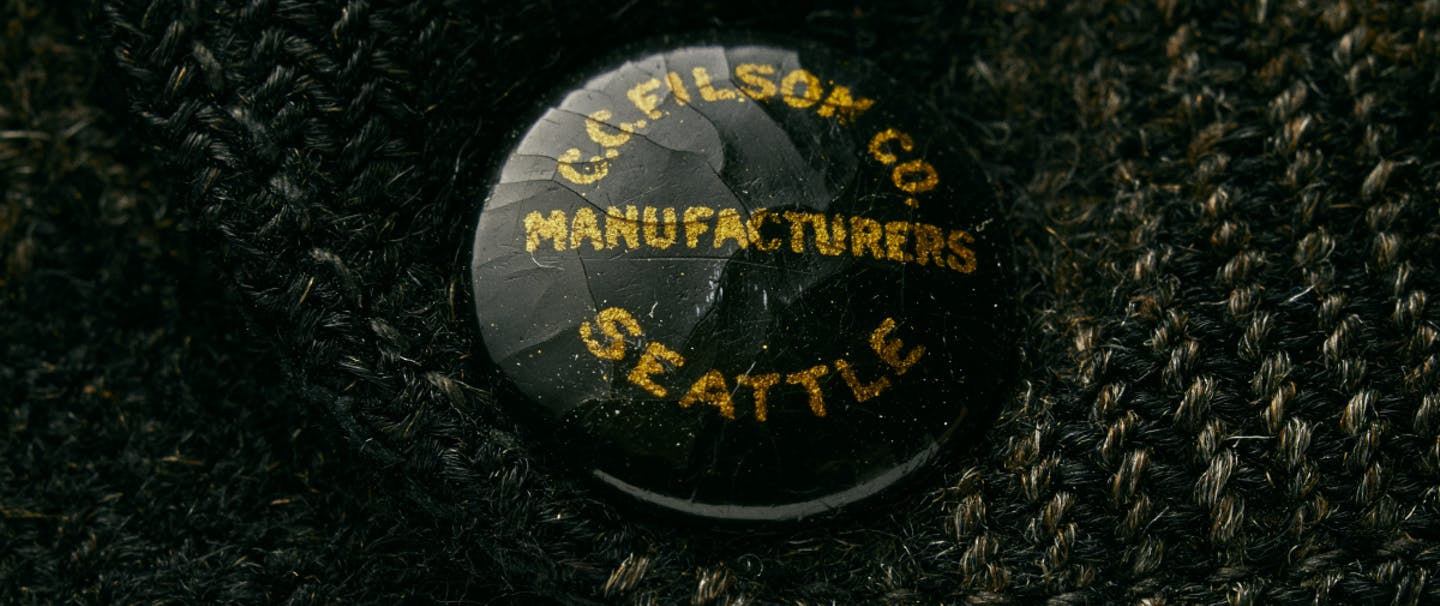 black button with gold lettering on knitted wool