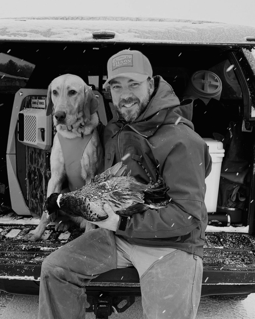 hunter in filson hat and heavy coat holds pheasant while sitting next to dog on truck bed