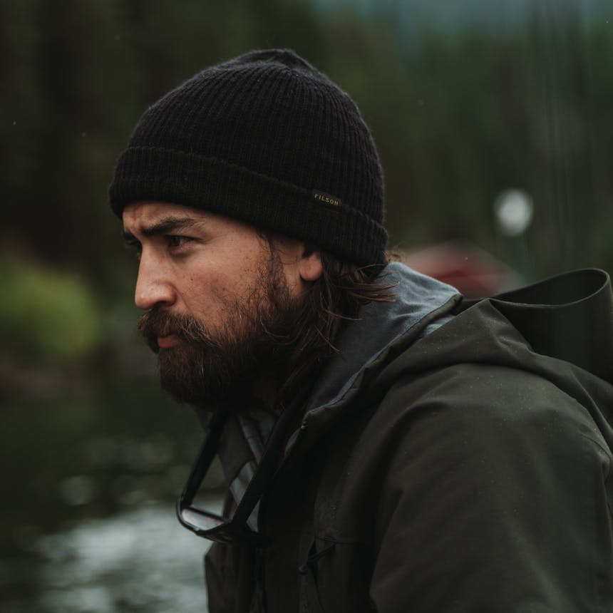 Man in black filson beanie and matte green jacket in forest with river in background