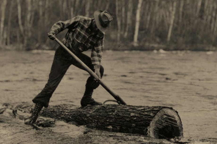 vintage sepia image of logger standing on log in river with logger tool