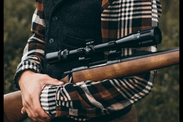 man in brown and white flannel holding hunting rifle with scope in grass field