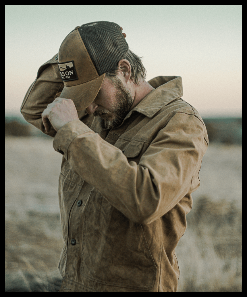man in tin cloth jacket puts filson trucker hat on standing in grassy field
