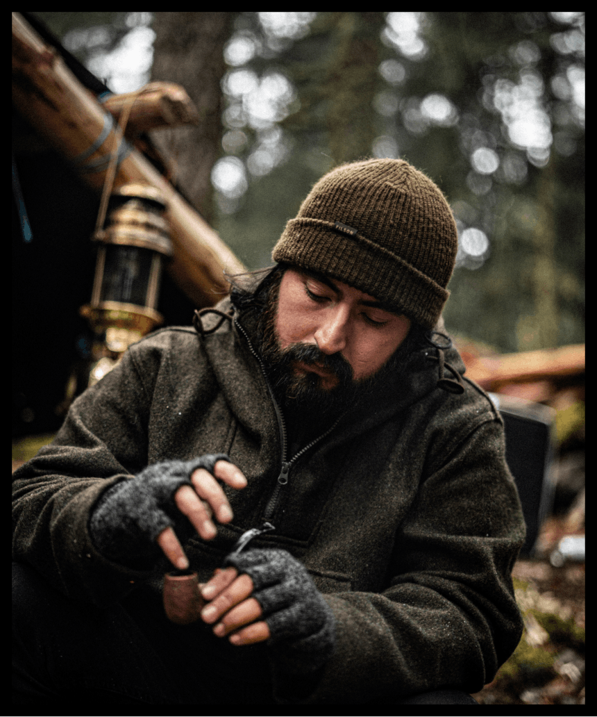 man packs a pipe win brown filson beanie and wool coat in forest