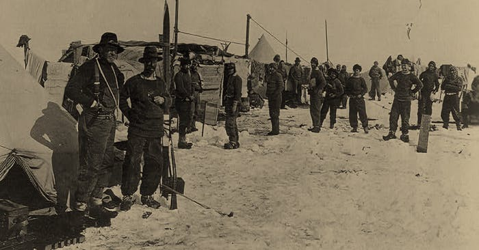 vintage black and white image of Men in black snow gear in a field with tents in a snowy field