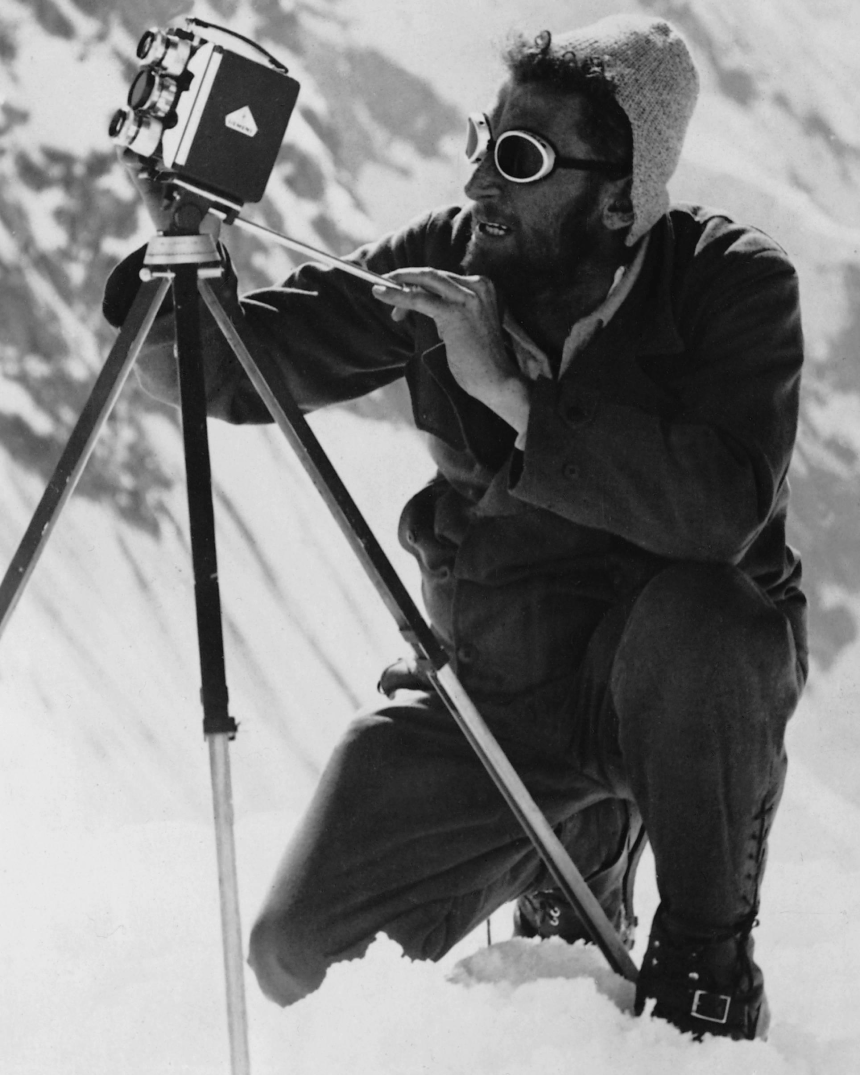 Man in gray hat and glacier goggles and black snow coveralls sets up a shot on a vintage film camera on the mountainside