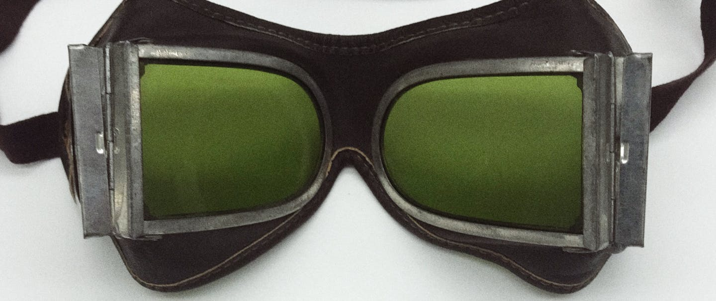 View from behind the lenses of old fashioned glacier goggles with olive green lens and metal trappings