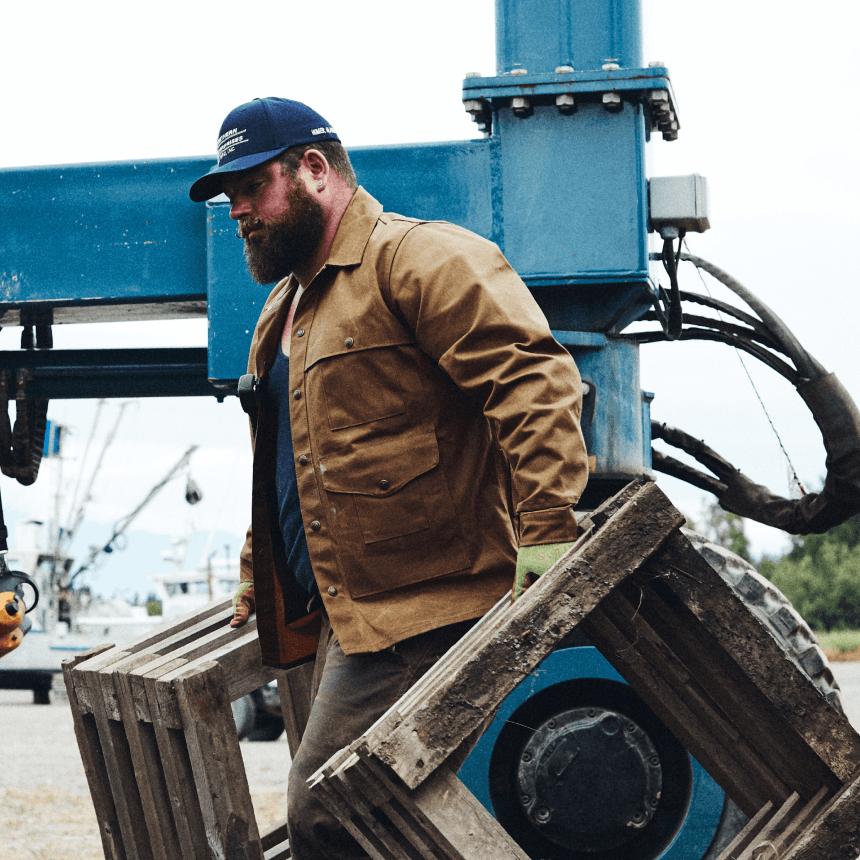 Man carrying wooden box frames in tan tin cloth cruiser jacket