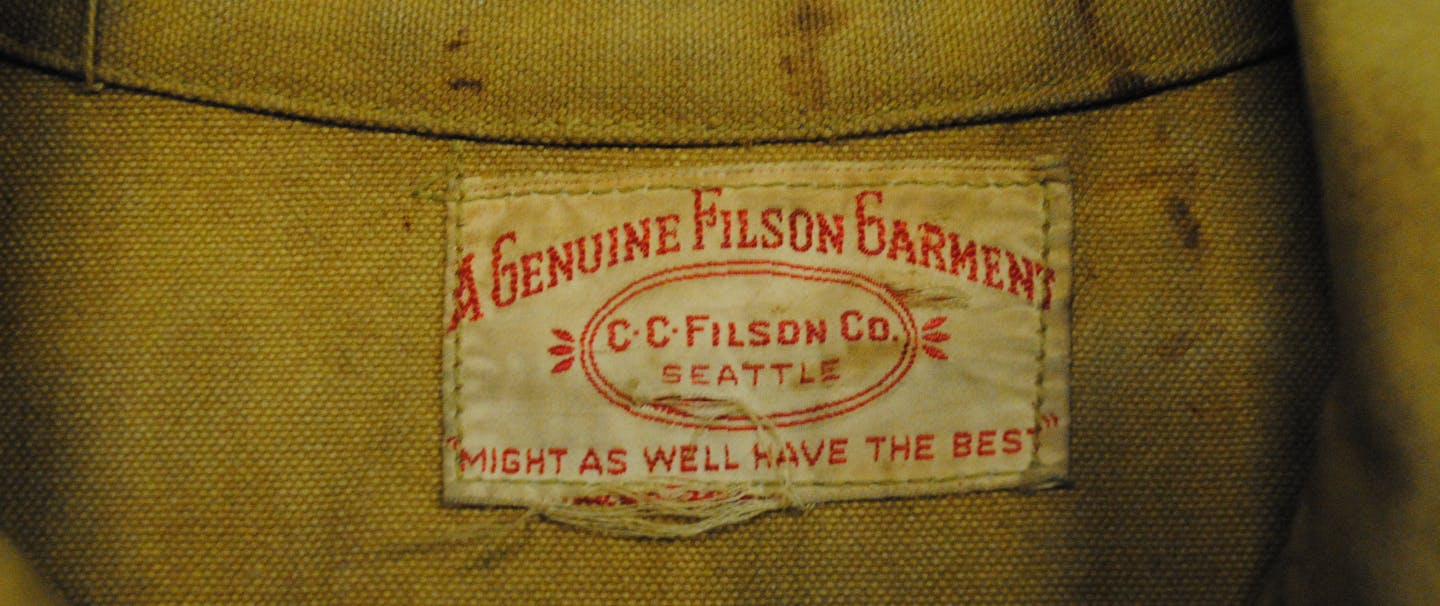 worn filson patch on tan cloth with patch text reads: A genuine Filson Garment CC Filson CO. Seattle