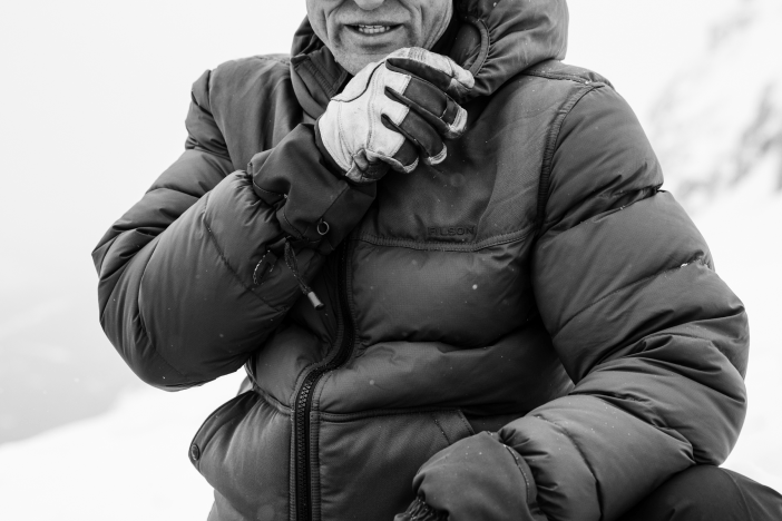 Black and White image of Man in Down Parka with glove on hand