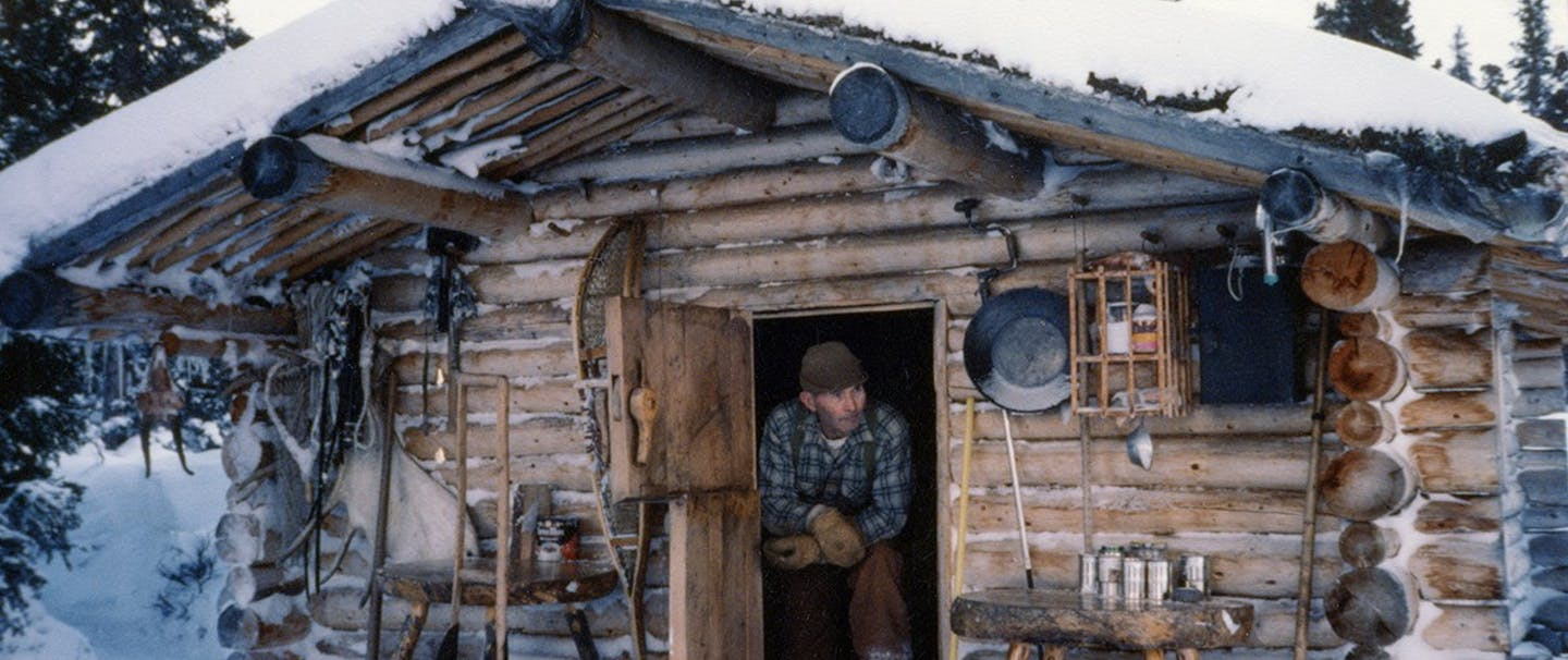 Richard Proenneke in his snow covered cabin in the forest