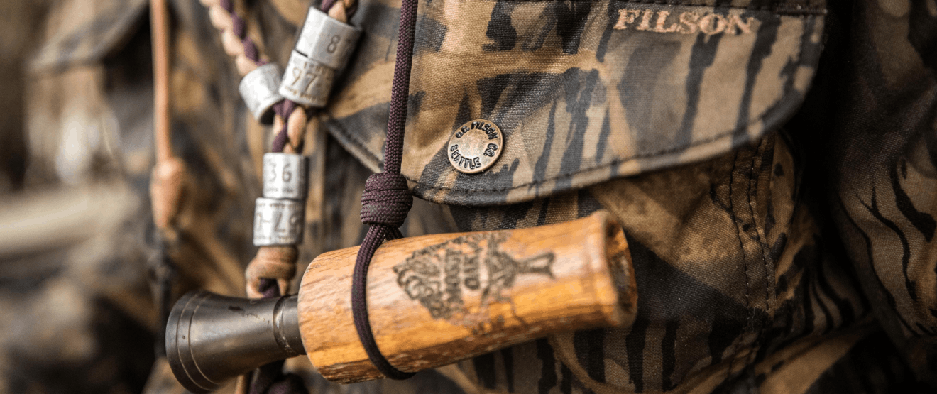 close-up image of duck call on a cord with filson camo jacket