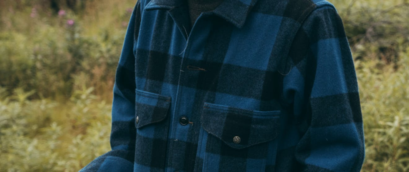 Man in meadow in heavy filson blue and navy blue plaid shirt