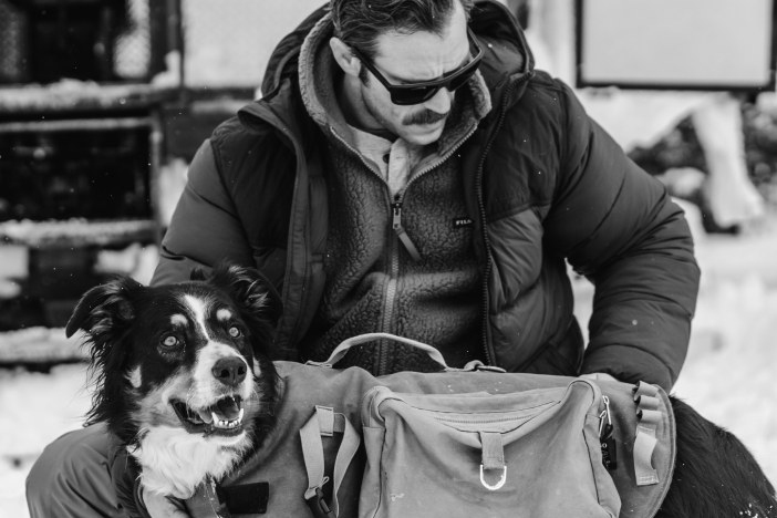 Man in Parka and FIlson Fleece affixing saddle bag to his dog