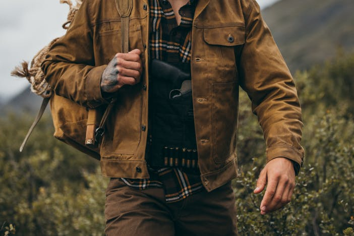 hunter with tan tin cloth jacket walks through low shrubbery with survival gear