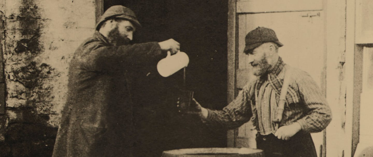 black and white image of man in black coat pours a drink out of a white pitcher for man in suspenders and plaid shirt