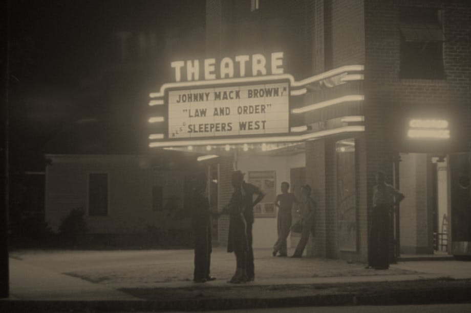 Black and white image of people standing in front of theatre with marquee reading